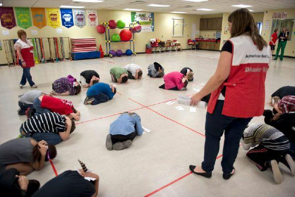 Red Cross worker Shannon Reed leads a class of Soldier Creek Elementary fifth graders in practicing a tornado drill. The Red Cross is visiting schools throughout the region, including this one in Midwest City, to teach