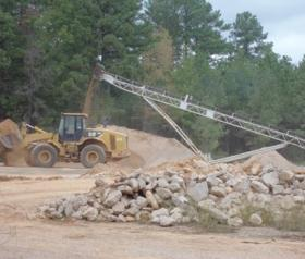 Concrete crushing equipment recycles building foundations once part of the Longhorn Army Ammunition Plant in Karnack, Texas. About 7,000 acres has been transferred to the U.S. Fish and Wildlife Service, which is returning the land to old growth forest.