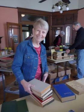 Janet Black arranges books at the Weisman-Hirsch House in Marshall, listed on the National Register of Historic Places.