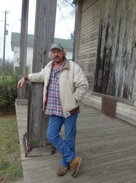 "Keachi artist Travis Whitfield stands on the porch of the shuttered Wyatt Bros. Mercantile where a group of African American men used to sit in rockers and tell stories of a bygone era. Whitfield documented the lives of the ""Porch Crew"" beginning in the 1970s."