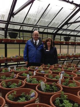 John Ross, a resident of Holy Angels for 39 years, stands in the new greenhouse with CEO Laurie Boswell.