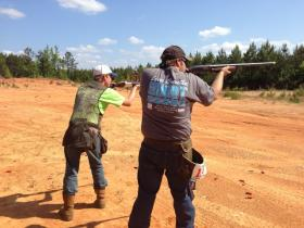 Kyle Peterson (right) sports a 4-H T-shirt that promotes the regional shooting sports competition.
