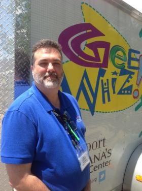 Sci-Port's education director Lou Papai stands next to the Gee Whiz Science Carnival trailer that hauls a collapsible, hands-on science exhibit.