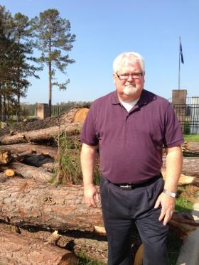 American Rose Center executive director Jeff Ware stands at the entrance where downed trees are piled up following a tornado on May 16.