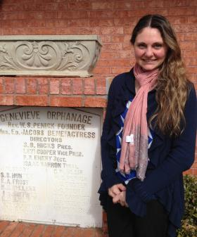 The Center for Families CEO Laura Brucia Hamm stands in front of her building, which features a dedication stone from the Genevieve Orphanage.