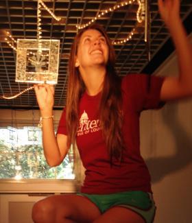 Centenary freshman Rebekah Frazier of Minden, La., hangs fleur de lis stained glass works from designs the students found in Paris.