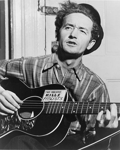 Woody Guthrie, half-length portrait, facing slightly left, holding guitar / World Telegram photo by Al Aumuller.