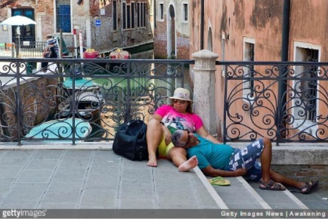 VENICE, ITALY - JULY 07: Two tourists rest exausted from the heat and the sun on a bridge on July 7, 2015 in Venice, Italy. An intense heatwave is sweeping across many regions in Italy, prompting local councils to issue a number of high level alerts.