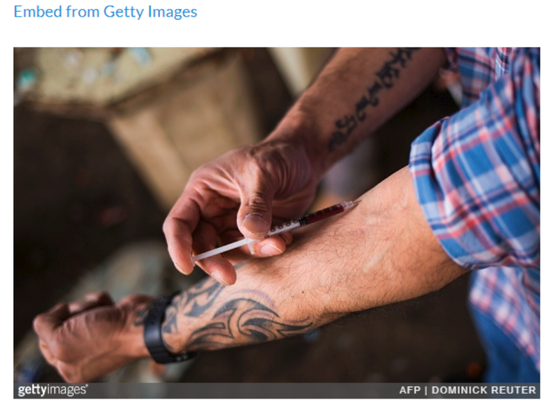 A man injects a shot of heroin near a heroin encampmentin the Kensington neighborhood of Philadelphia, Pennsylvania, on April 14, 2017.