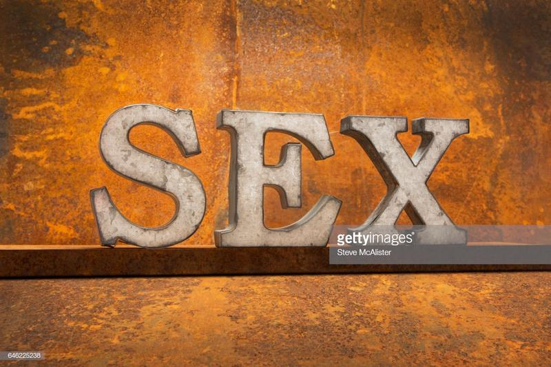 Metal Letters spelling out word SEX on Rust Background