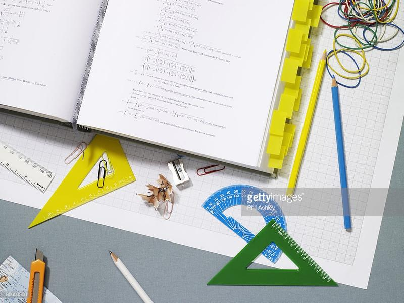 Mathematical book open with stationery on graph paper