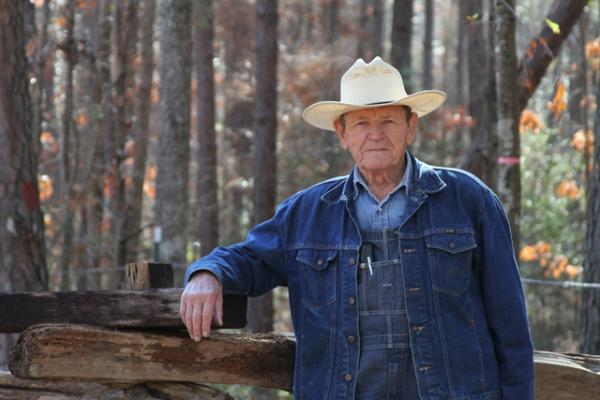 E.J. Adams, 81, restores cemeteries in Panola County. He stands by cedar logs that were part of the original fencing at Gary Family Cemetery in Carthage.