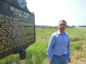 Vic Zimmerman stands next to the sign commemorating Ruskin Park.