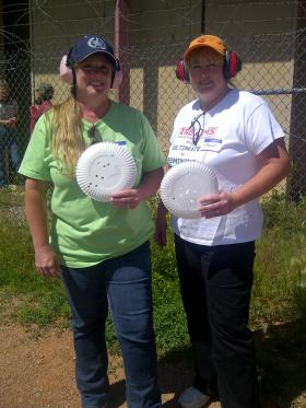 Twins Julie and Jodie show off their shooting skills by holding up paper plate targets riddled with bullet holes.