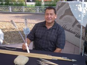 Mike Marshall holds tool used for buffalo-rib throwing game – among the items on display at his traditional Lakota games booth.
