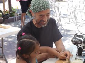"Woodworker Tadao Arimoto helps 3-year old Rheanna Whiteman make a traditional Japanese toy called a ""yajirobei""."