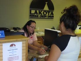 Lakota Federal Credit Union teller Shayna Richards counts out money for a credit union member.