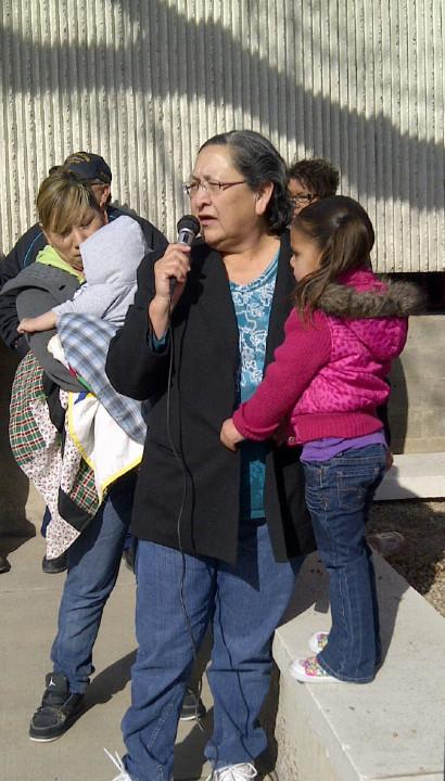 Cordelia White Elk of Oglala Sioux Tribe speaks while holding her granddaughter.