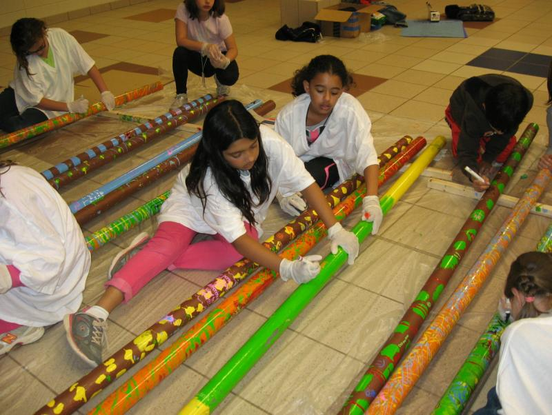 Children write on decorated metal pipes that will form the body of the sculpture.