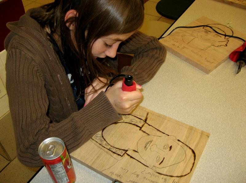 Ashley Grandpre burns her image into an oak panel  that will form part of the sculpture. Ashley is one of the children chosen to go to L.A. at the end of July.