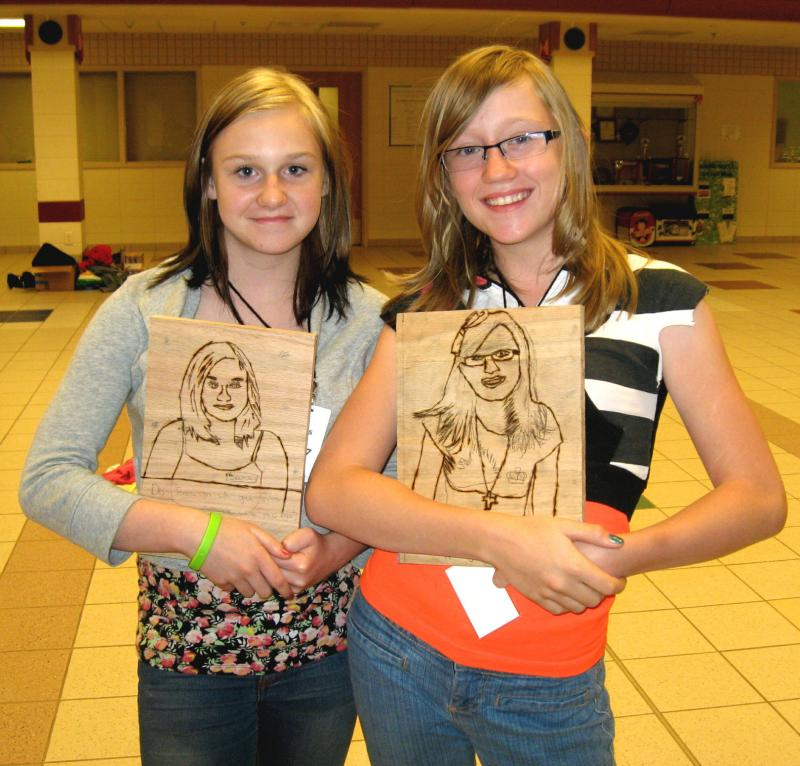 Seana Birkenbuel, left, and Katey Miracle show off their portraits burned into oak panels. These are part of the sculpture that is coming back to Rapid City eventually.