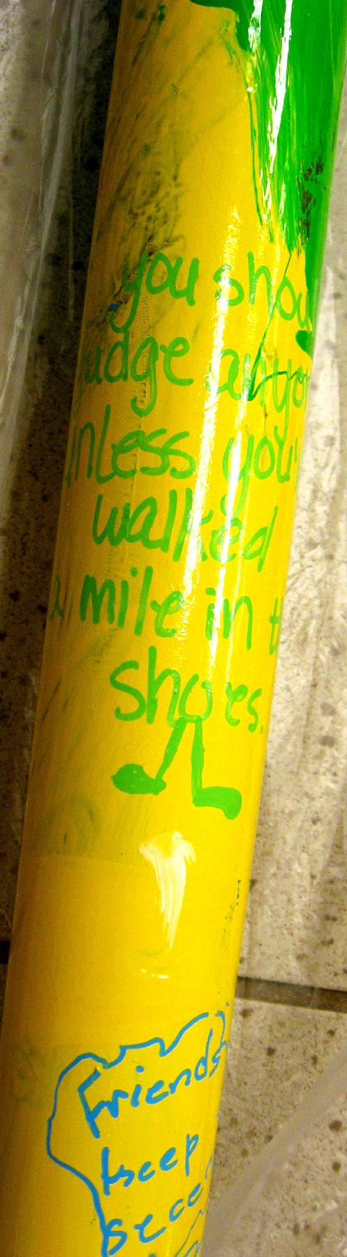 Close-up of the messages children wrote on the painted metal pipes.