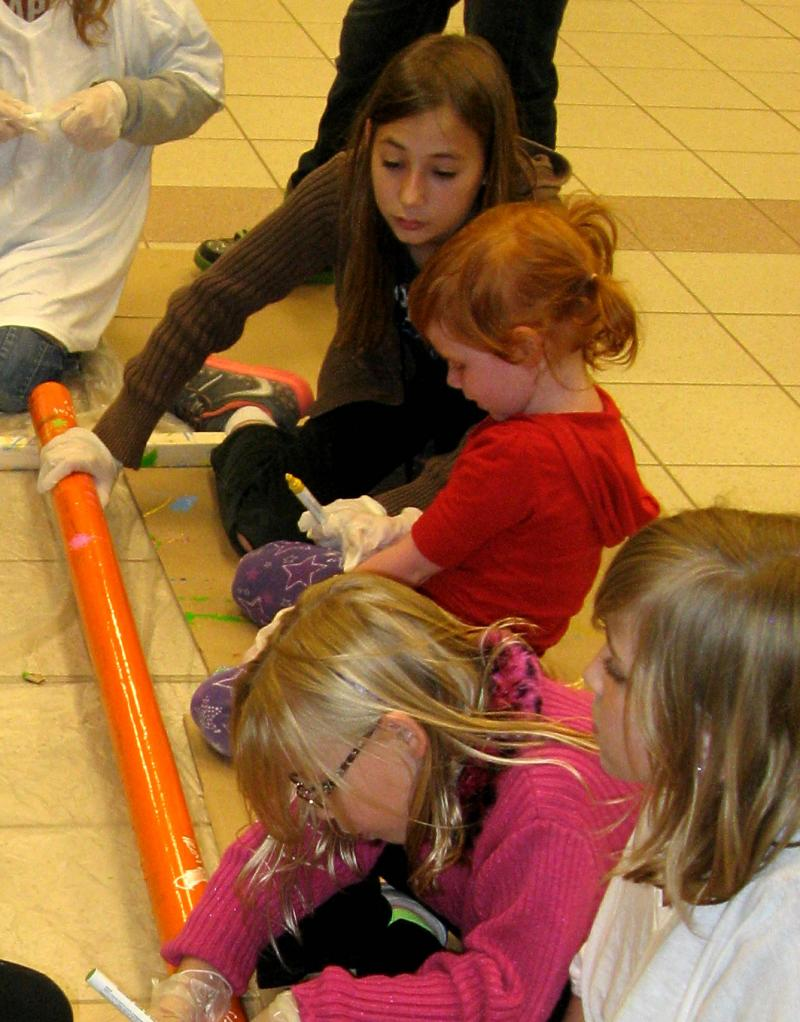 At top, Ashley Grandpre helps four-year-old Lily Sortland write on a painted pipe.