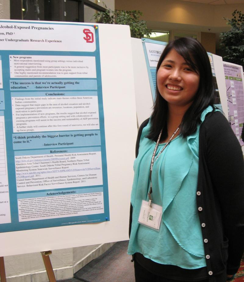 Shanice Nez stands beside the poster illustrating her research into alcohol exposed pregnancy.