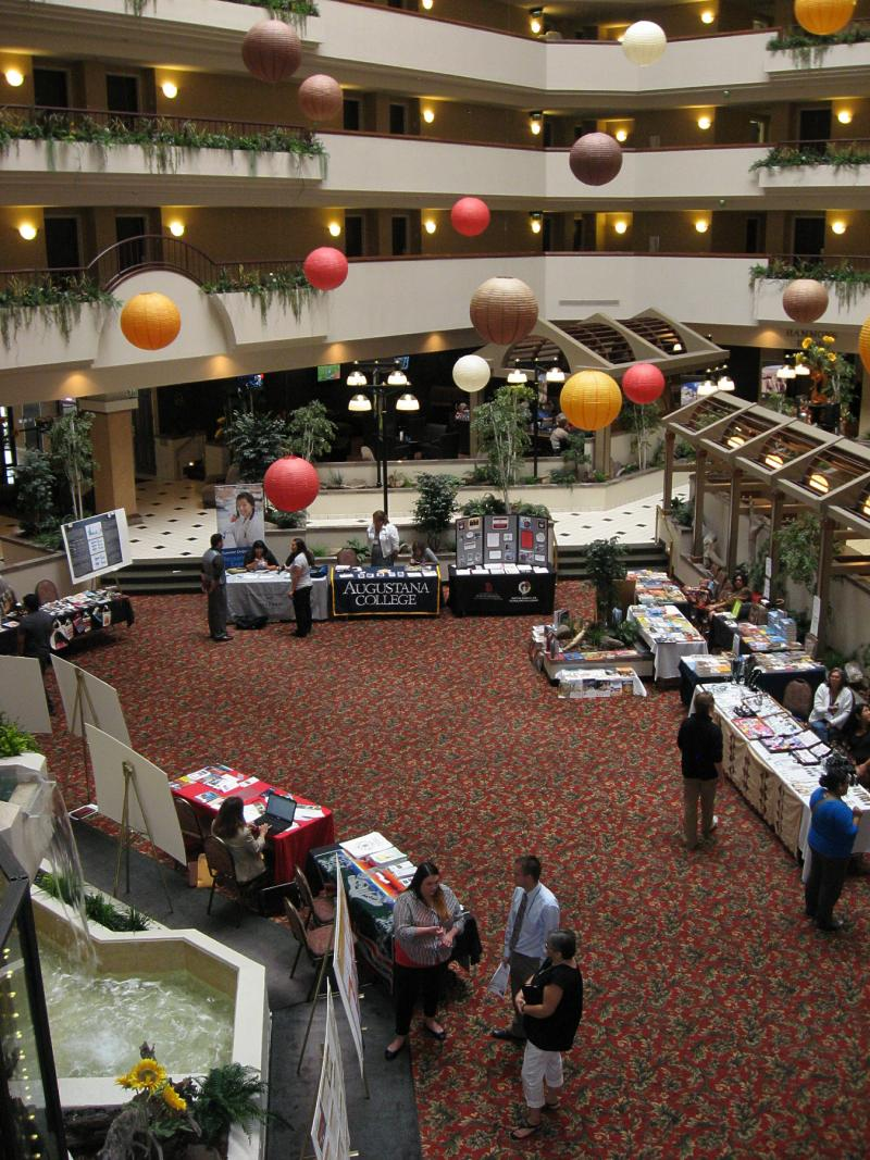 In the lobby of the Rushmore Plaza Holiday Inn, student researchers present their work on posters (left) while artisans sell their wares (right).