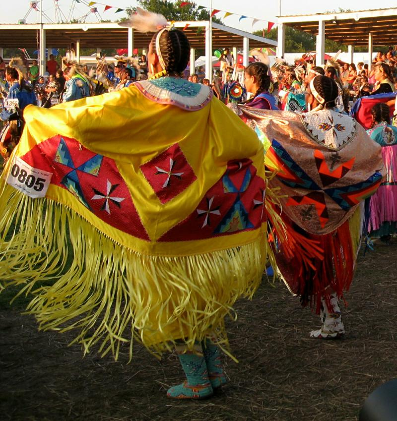 Women wear swirling shawls at the powwow.