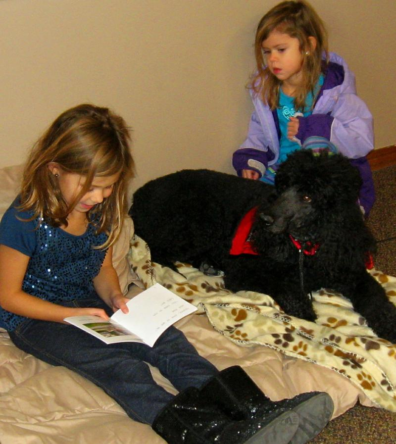 Kylie Jorgensen reads to Rhett while her little sister, Cadence, listens.