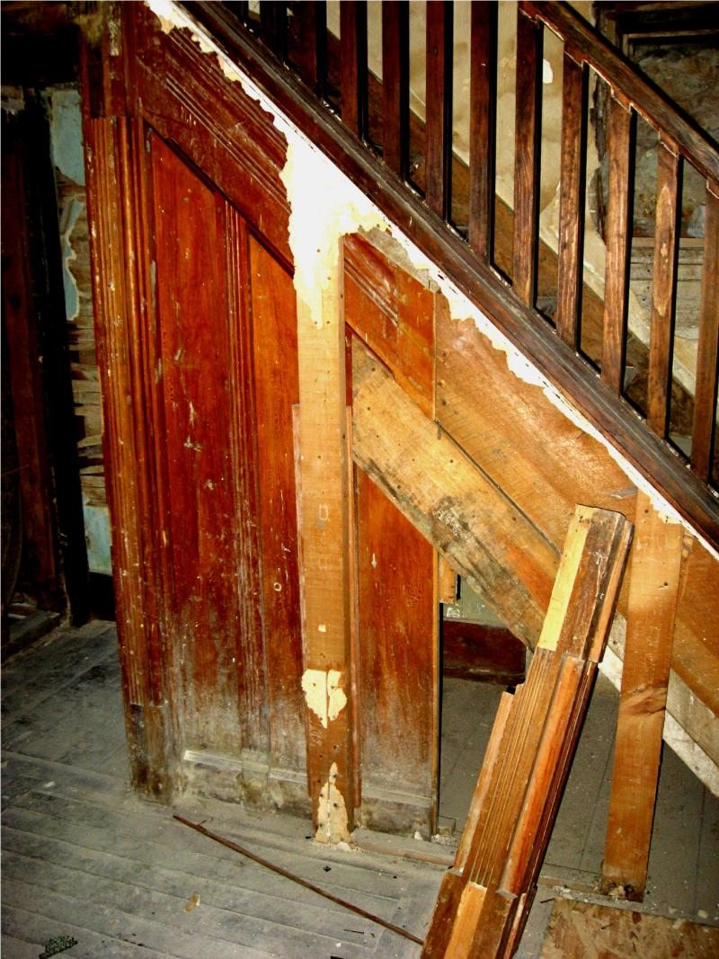 When workers tore sheet rock off this space below the stairs, they found original paneling.
