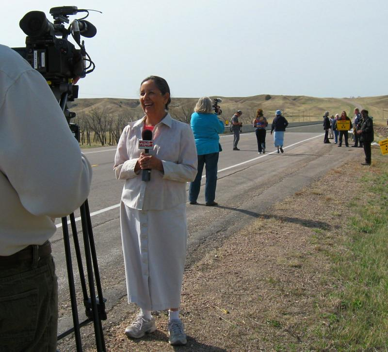 Charmaine White Face gives interviews to journalists on the bridge over the Cheyenne River.