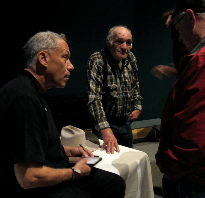 Jon Alpert, left, and Vernon Sager autograph DVDs and talk with audience members.