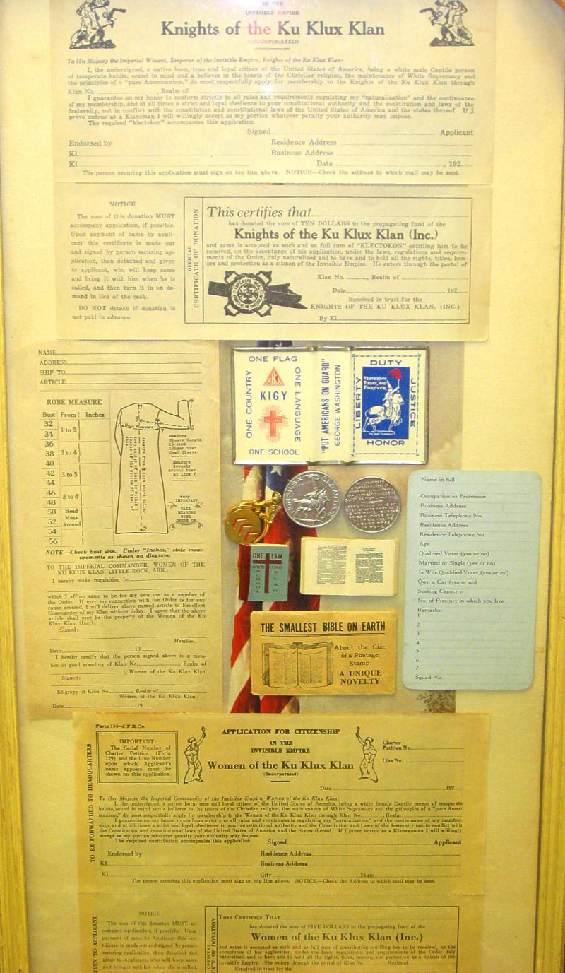 A framed collection of KKK artifacts. The grouping at center right includes the world's smallest Bible.