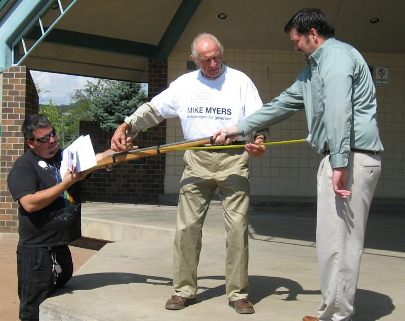 Mike Meyers, center, measures the distance from a fake shotgun barrel to the abdomen of the man on the right. At left, a staffer holds the butt of the gun off the ground.