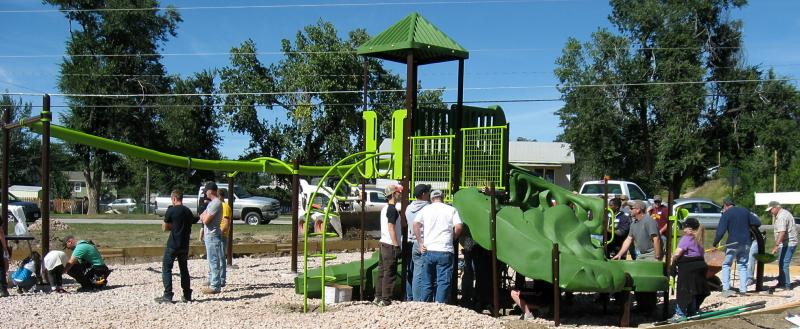 "By the end of the day, the ""neon green and dark green"" playground equipment has been installed."