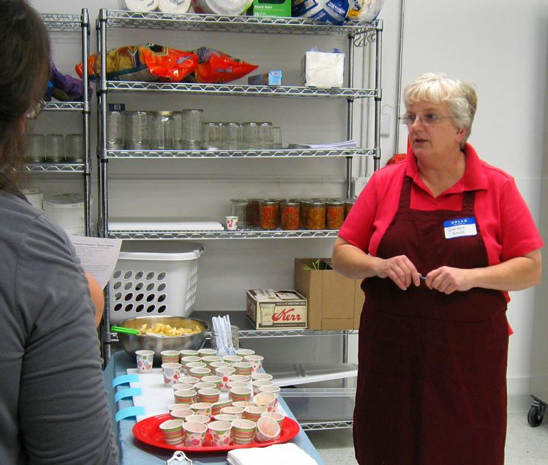 Staff member Darlene Stulken talks about nutrition. In the background, on shelves, are jars of salsa made from local tomatoes, peppers, and onions.