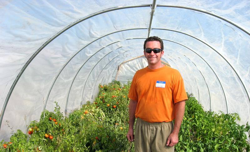 Volunteer Will Giordino shows off the tomato plants in the hoop house.