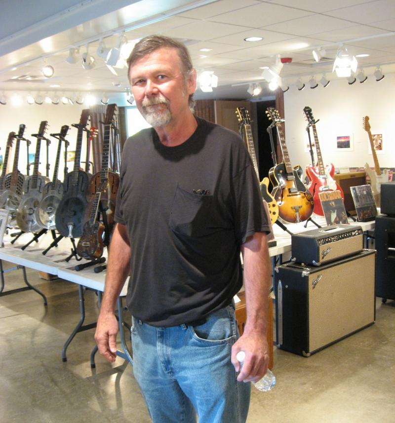 Mark Falk, with his collection of metal-body guitars behind him to the left.