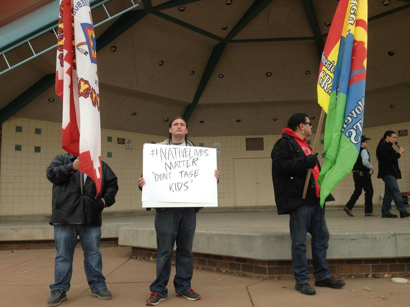A young man holds a sign at the start of Rapid City's protest against police brutality on Friday