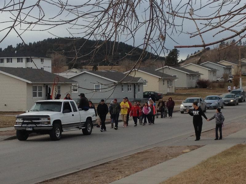 A rpocession and prayer service in Lakota Homes following a police shooting incident on Saturday.