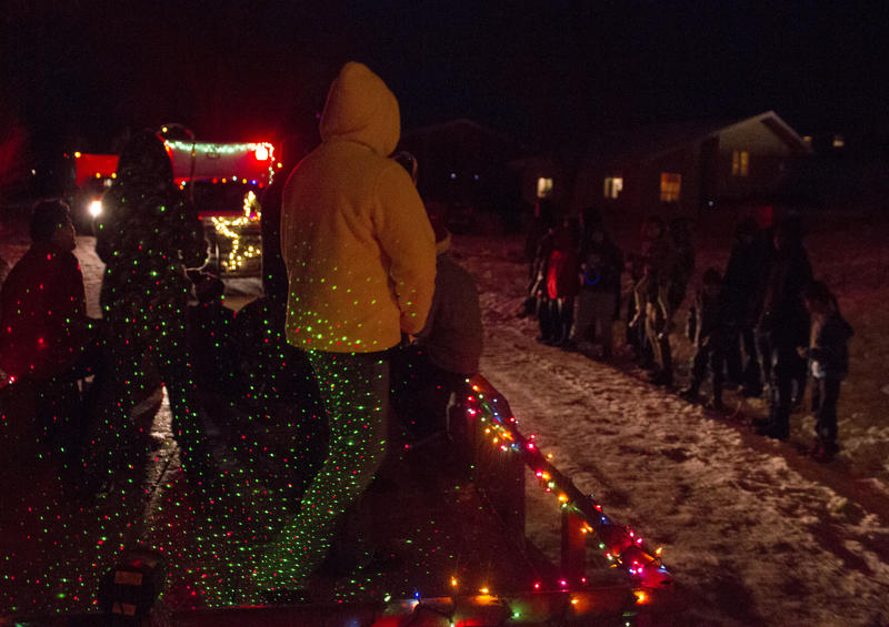 Members of the bear program yell holiday greeting to resident of Pine Ridge during the parade of lights.
