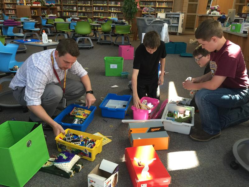 Integrationist Travis Lape works with students to sort makerspace supplies