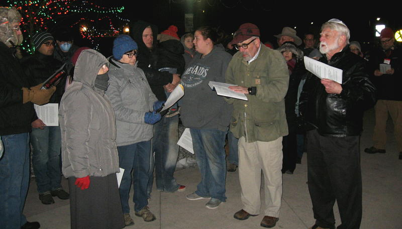 "The group sings ""Rock of Ages."" At right forefront, dressed in black, is Stan Adelstein, who donated the menorah and led the ceremony."