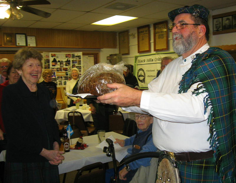 Bill Knight presents the haggis to the revelers.