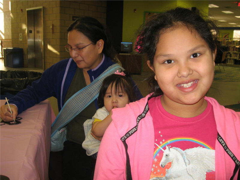 Amelia looks forward to balloons dropping on her. In the background, her mother works on a mask and holds Baby Sister.