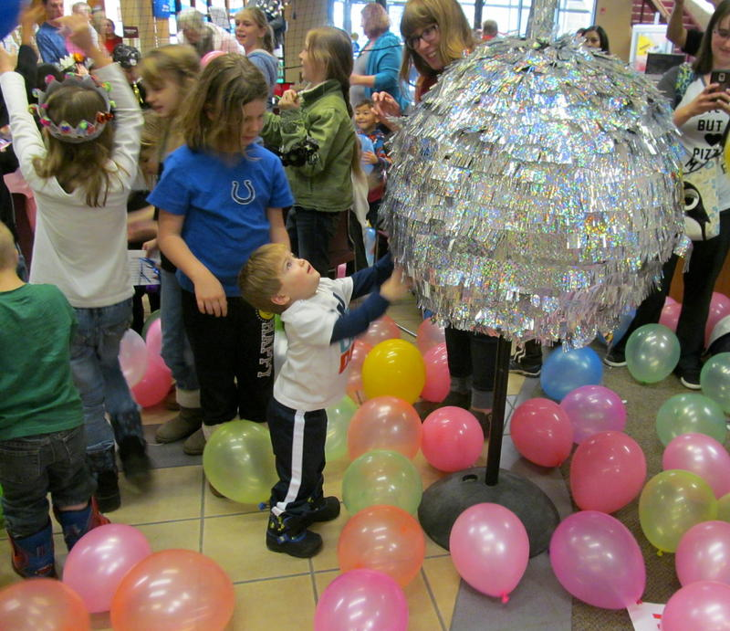 "A child examines the ""shaggy disco ball"" that dropped from the ceiling."