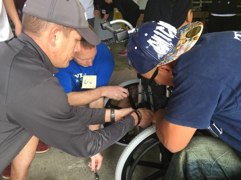Dispatch volunteers help adjust a wheelchair at a Hope Haven distribution in Guatemala.