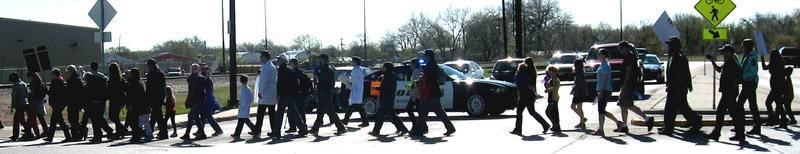 Marchers cross the street, with Rapid City police officers protecting the crosswalk..